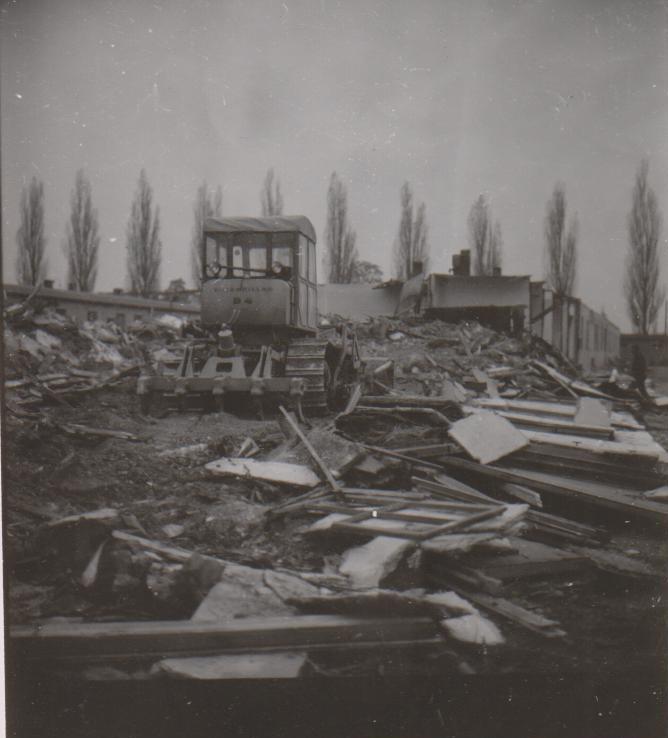 בחזית התמונה שרידי צריפים שנהרסו זה עתה על ידי דחפור הנוסע לעבר חלקי צריפים אחרים שעדיין עומדים. (זכויות יוצרים של התמונה: אתר ההנצחה של מחנה הריכוז דכאו).