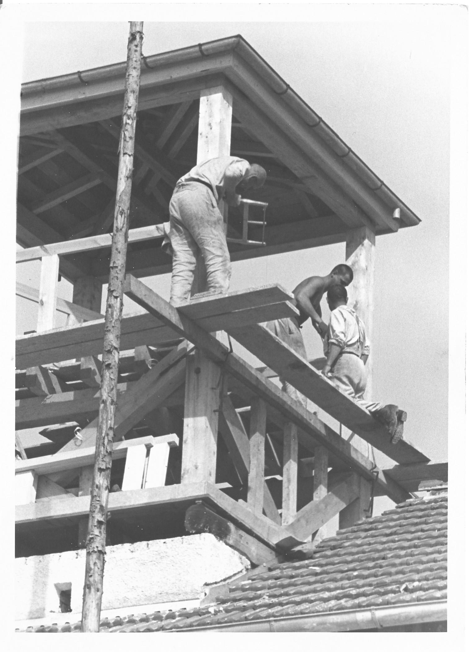Tre detenuti che lavorano alla costruzione della torre di guardia, in legno, sul Jourhaus, immagine propaganda delle SS (Diritti di immagine: Bundesarchiv)