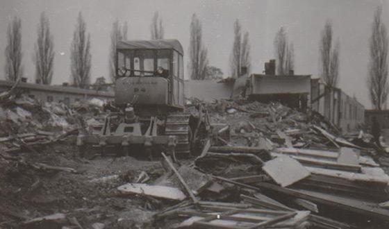 Na pierwszym planie widać pozostałości baraku, po których przejeżdża spychacz, kierując się w stronę jeszcze stojącej części baraku. (Muzeum-Miejsce Pamięci Dachau)