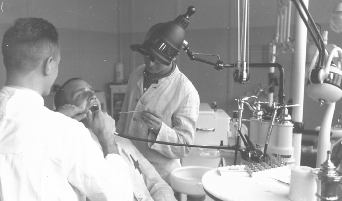 The photograph shows a prisoner being treated by two dentists in a dental surgery that is well equipped for the time.