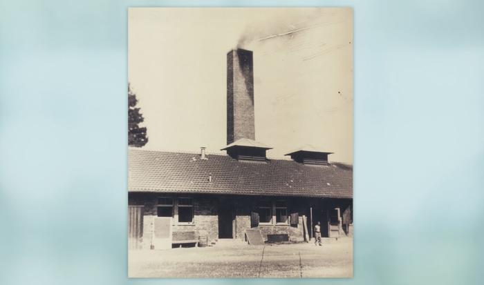 """Auf dem Foto ist der Teil der """"Baracke X"""" zu sehen, auf dem der große Kaminschlot in den Himmel ragt, aus dem dunkler Rauch in den Himmel strömt. Ein Mann, der nur mit Hosen und Schuhen bekleidet ist steht vor dem Gebäude, an dem alle Türen und Fenster weit geöffnet sind."""
