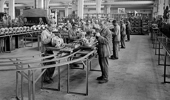 Więźniowie montują elementy przy ruchomej taśmie produkcyjnej (BMW Group Archiv, München)