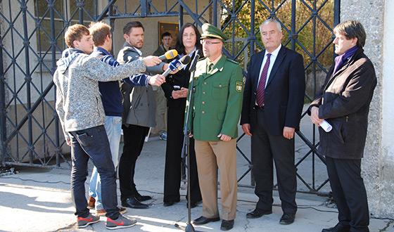 Conférence de presse devant le Jourhaus. À l'arrière-plan, on aperçoit le portail, dont la porte est manquante. De gauche à droite: des journalistes; Gabriele Hammermann, directrice du mémorial du camp de Dachau; Thomas Rauscher, chef de la police de Dachau, et Ludwig Spänle, ministre de la Culture de Bavière (Crédits photographiques: Mémorial du camp de Dachau)