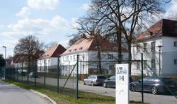 Hinten: Die ehemalige SS-Siedlung. Rechts vorne: Informations·tafel 7 vom Weg des Erinnerns. Das Foto ist von 2017. (KZ-Gedenk·stätte Dachau)