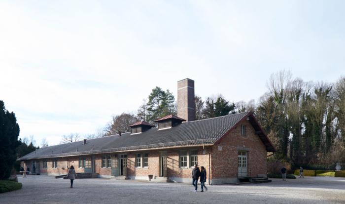 """Das neue Krematoriumsgebäude, das auch """"Baracke X"""" genannt wird, ist ein längliches Backsteingebäude mit einem großen viereckigen Kaminschlot. Das Gebäude verfügt über mehrere Eingänge, die durch Rampen oder Stufen zu erreichen sind."""