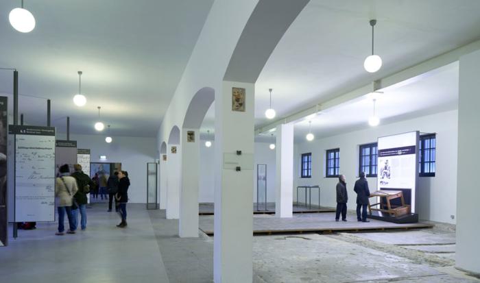 Alternativtext: Auf der linken Seite im ehemaligen Häftlingsbad finden sich Ausstellungstafeln. Getrennt durch mehrere Bögen im Mauerwerk ist auf der rechten Seite des Raumes ein Teil der tiefergelegten Wanne freigesetzt.