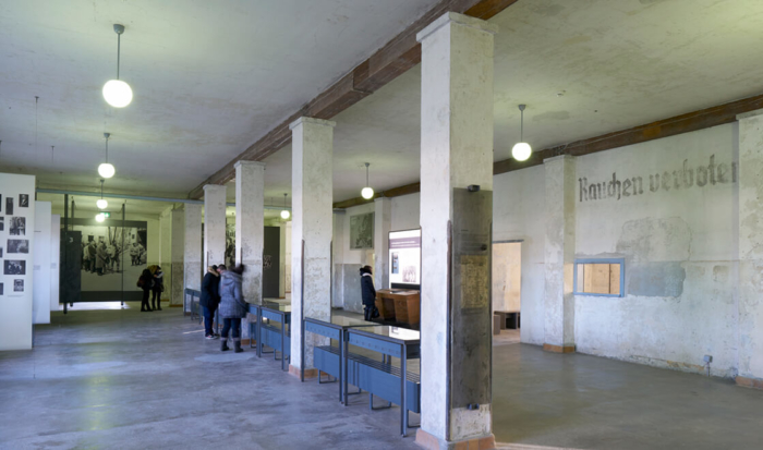 The shunt room is divided down the middle by a row of pillars. The display cases positioned between the pillars are where large wooden tables with file cards once stood for the admission procedure of newly-arriving prisoners.