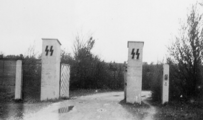 The photo shows two tall square stone gateposts with the emblem of the SS. The gate is open.