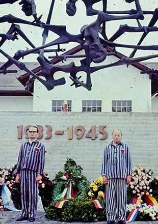 """Pod rzeźbą Pomnika Narodów stoją dwaj byli więźniowie w pasiakach. Obok nich liczne wieńce, które są oparte o mur z napisem """"1933-1945"""". (Daniel Gordana i Gabriel Glid)"""