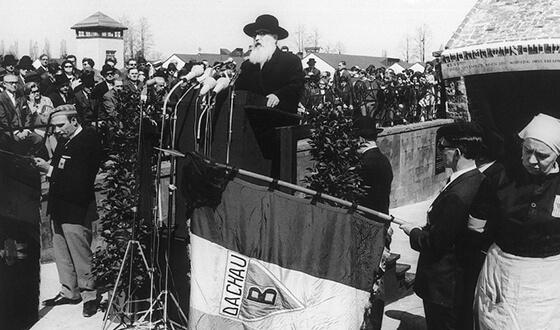 Le rabbin David Spiro se tient sur une tribune devant le mémorial juif et récite la prière des morts devant plusieurs micros. On voit à l'arrière-plan une foule de spectateurs.