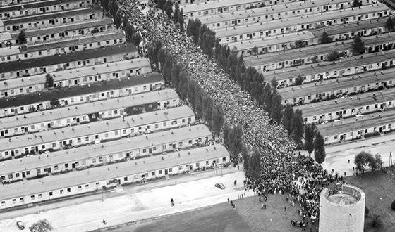 Zdjęcie lotnicze przedstawiające były obóz więźniarski od strony Kaplicy pw. Lęku Chrystusa Przed Śmiercią. Byłą ulicę obozową wypełnia tłum ludzi. (Luftbildverlag Bertram)