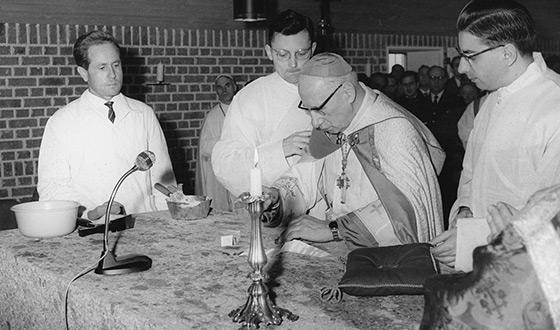 Johannes Neuhäusler w szatach liturgicznych i w otoczeniu trzech ministrantów przed ołtarzem kościoła klasztornego. W tle widać uczestników mszy. (archiwum Karmel Dachau)