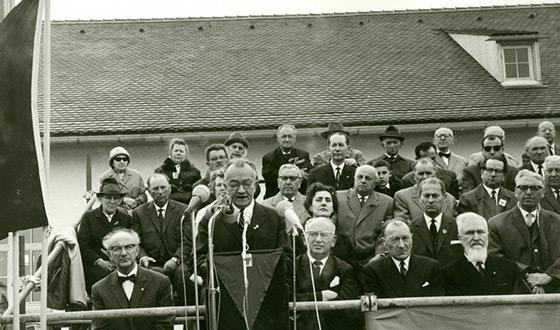 Widok trybuny przed byłym budynkiem gospodarczym, na której siedzi ok. 30 osób. Stojący na mównicy przemawia do mikrofonu. (CID)