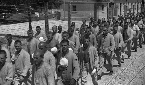 Więźniowie z miskami emaliowanymi w dłoniach, ustawieni w szeregach. Zdjęcie propagandowe SS (Archiwum Narodowe)
