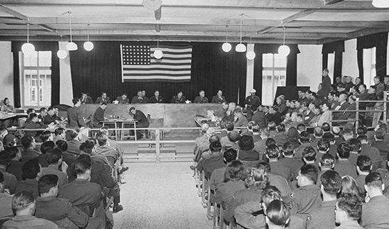 La salle du tribunal selon la perspective des spectateurs: Derrière le banc des juges sont assis huit juges, le drapeau américain est suspendu derrière eux. Une vingtaine d´accusés sont assis à droite du banc des juges, et devant celui-ci ont pris place les greffiers. Les rangées de spectateurs sont remplies.