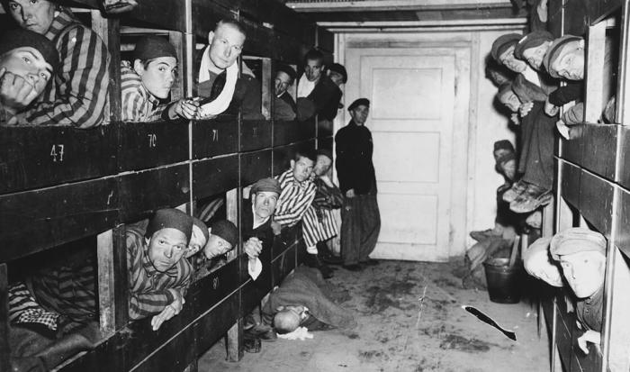 Der Fotograf hielt auf dem Bild den Blick in einen Gang fest, der rechts und links von aneinandergereihten Betten umgeben ist. In den Stockbetten sind mehrere Häftlingen in Sträflingskleidung zu erkennen, die ihren Kopf aus den hölzernen Pritschen recken. Einige von ihnen schauen direkt in die Kamera.