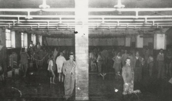 Alternativtext: Einige halbbekleidete Häftlinge und Gefangene in gestreifter Häftlingskleidung stehen unter den Duschköpfen im Häftlingsbad.