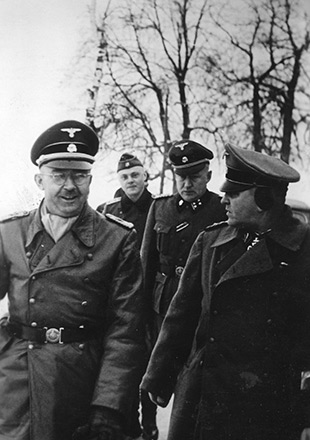 Heinrich Himmler et Theodor Eicke d'humeur joyeuse lors de leur visite au camp de Dachau en 1934, photographie de propagande SS (Crédits photographiques : Archives fédérales allemandes)