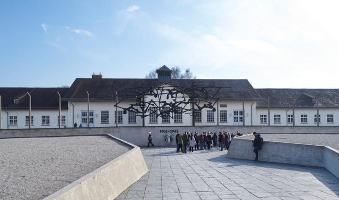 Sulla foto vediamo un sentiero che conduce al monumento commemorativo internazionale. Sul muro con la scritta 1933 - 1945 è installata una scultura in bronzo che raffigura uomini sul filo spinato. Sullo sfondo ci sono pilastri in calcestruzzo che simboleggiano il sistema di sicurezza.