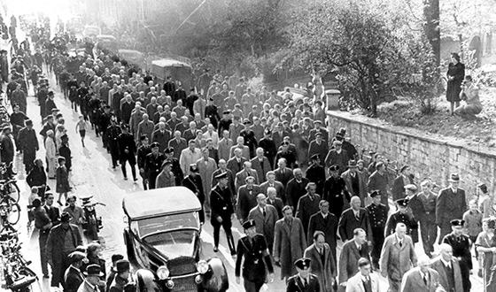 Scores of men in coats walk down a street in Baden-Baden, escorted by SS men in uniform – onlookers line the street, SS propaganda photo (Federal archives)