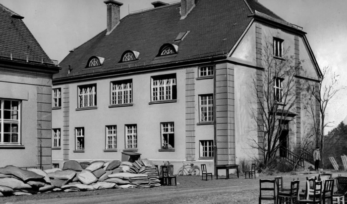 The three-storied commandant's headquarters has many windows and is located directly next to the prisoners' camp. The photograph shows the rear of the building, which was built in the style of a villa.