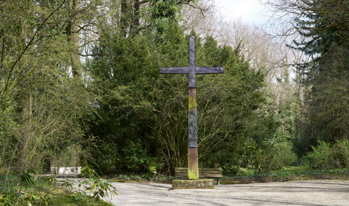 Surrounded by trees and bushes, a large cross was erected on a gravel path.