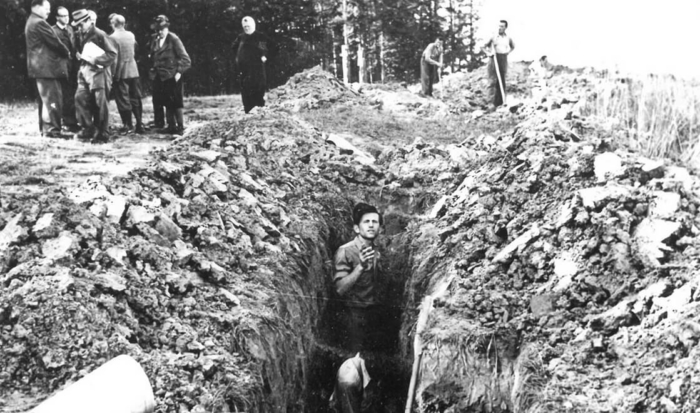 The photo shows a man up to his shoulders in a trench. Piled up on the left and right are earth and bones.