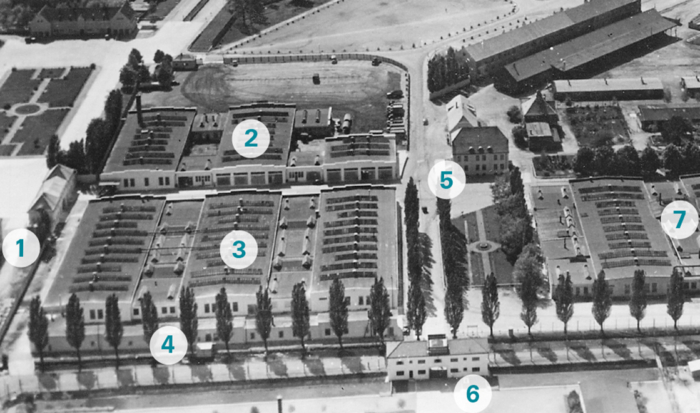 The aerial shot in black and white, which shows a section of the former SS grounds, features numbers designating seven individual building complexes and locations. The adjoining camp grounds are in the lower part of the photo.