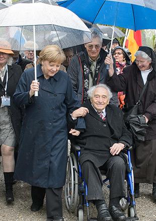Texte alternatif: La chancelière allemande, Angela Merkel, marche aux côtés du survivant du camp de Dachau, Max Mannheimer, assis dans un fauteuil roulant. Max Mannheimer lui donne le bras. (Crédits photographiques: Sebastian Freller)