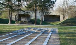 Vorne: Installation Ort der Namen (2014). Hinten: Denk·mal für die sowjetischen Kriegs·gefangenen und der ehemalige Schieß·stand. Das Foto ist von 2017. (KZ-Gedenk·stätte Dachau)