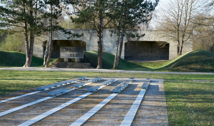 Hidden somewhat by trees, two shooting stands are located in the background. The shooting lanes are bordered on the left and right by the grassy mounds. In front of the shooting stands is a stone monument dedicated to the murdered Soviet prisoners of war. In the foreground are the long rows of parallel stone slabs, embedded into the ground. Mounted on some of the slabs are commemorative plaques for the identified victims amongst the Soviet prisoners of war.