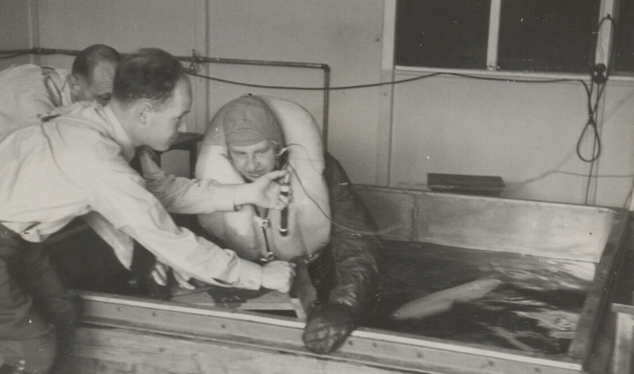 Wrapped up in thick clothes and wearing a life vest, a prisoner sits in a shallow water basin. While forced to endure the life-threatening hypothermia experiment, two SS men stand next to the basin. Leaning forward they are measuring the prisoner's responses to the extreme cold.