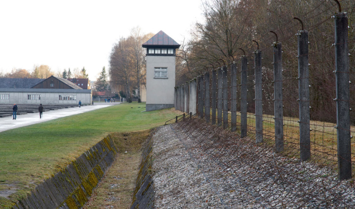 The reconstructed guard installation is made up of the following: on the camp grounds is a patch of grass; to its right is a two-meter deep ditch, a barbed-wire obstacle fitted to the upward slopping strip between the other side of the ditch and the electrified barbed-wire fence. A reconstructed square guard tower is in the distance.