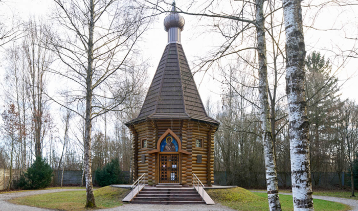 Located on the way to the memorial area of the crematorium on the left-hand side, after crossing the bridge over the Würm canal, is the Russian Orthodox chapel. An octagonal timber structure built in a simple cabin style, it stands in the middle of a quiet, tree-lined lawn. The steep tent shape recalls traditional Russian architecture, while a Russian cross is positioned on top of the shingle-clad roof hood. An icon of the Mother of God with a child is mounted over the entrance.
