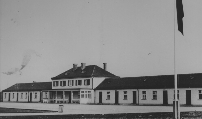 The maintenance building was a long, single storied structure with a two-storied main section between the two wings. An open porch-like annex is on the ground level; roofed over, benches are arranged to face roll call area.