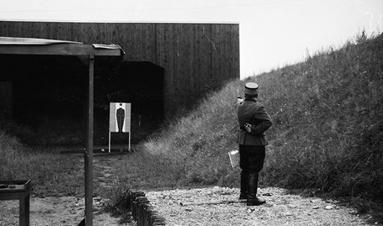 Esesman z wyciągniętą ręką, w której trzyma pistolet, celuje do tarczy w kształcie człowieka (Heinz Bielmeier, Dachau)