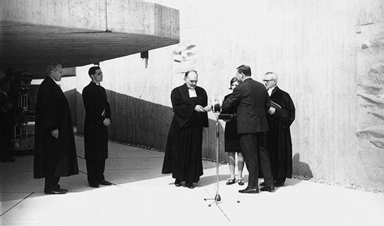 Devant l'entrée de l'église de la Réconciliation, l'architecte Helmut Striffler remet la clé à l'évêque Kurt Scharf (au centre), vice-président du Conseil des églises évangéliques d'Allemagne (Crédits photographiques: Keystone)