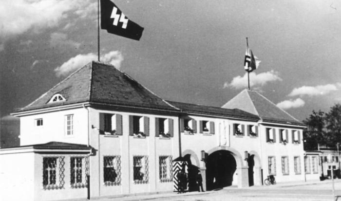 Ein beeindruckendes Gebäude mit Torbogen, vor dem ein Wachmann positioniert ist und das mit SS- und Hakenkreuzsymbolen beflaggt ist.