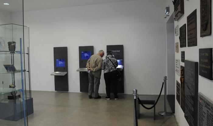 """Entrando nella sala commemorativa troviamo, sul lato destro, tre terminali che danno la possibilità di ricercare i caduti nel campo di concentramento di Dachau sulla base dei nomi nel cosiddetto """"libro commemorativo""""."""