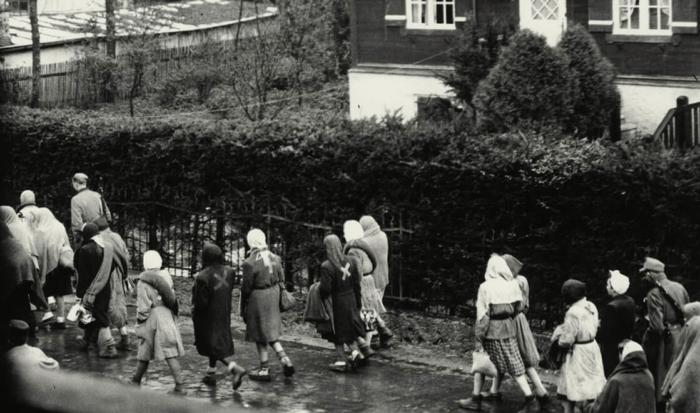 Da una finestra viene fotografata una marcia di donne. Sulla testa portano sciarpe per proteggersi dalla pioggia. Inoltre tante hanno una coperta avvolta intorno al corpo, che usavano per l'accampamento notturno. Sulla parte sinistra dell'immagine riusciamo a individuare un uomo delle SS armato.