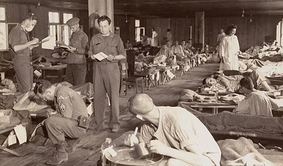 Więźniowie w szpitalnych koszulach na pryczach. Opiekują się nimi amerykańscy żołnierze (USHMM)