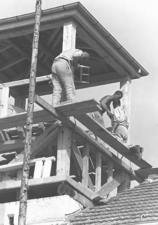 Trzej więźniowie podczas budowy drewnianej wieży strażniczej na dachu Jourhausu, zdjęcie propagandowe SS (Archiwum Narodowe)