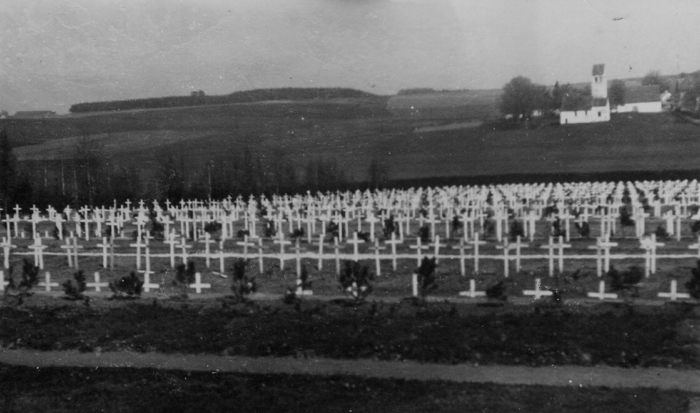 A large number of white crosses are erected in parallel rows on the gravesite at the woodlands cemetery. A church is visible in the background.