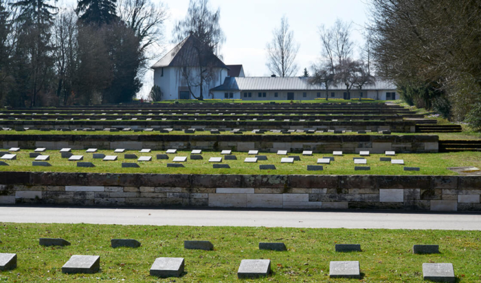 Positioned parallel behind one another are a number of elevated mass graves. Stone slabs remember the dead.