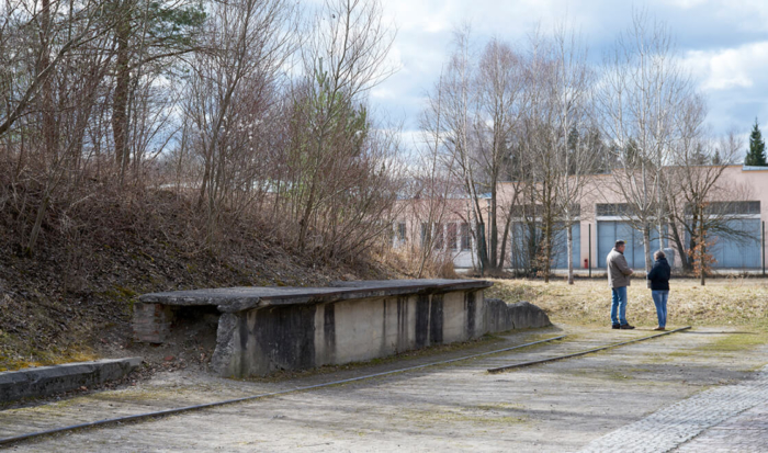 Made of demolition material, an embankment wall with trees adjoins the remnants of a rail track. This is located on the left side of the former connecting road to the SS camp. The former camp bakery is in the background.