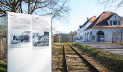 Links: Informations·tafel 4 vom Weg des Erinnerns Mitte: Gleis·stück an der Isar-Amperwerke-Straße Das Foto ist von 2017. (KZ-Gedenk·stätte Dachau)