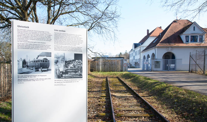 """The section of rail line in the middle of the photo led to the former SS grounds. A panel of the """"Path of Remembrance"""" is in the foreground; it provides information on the purposes this still preserved section once served."""
