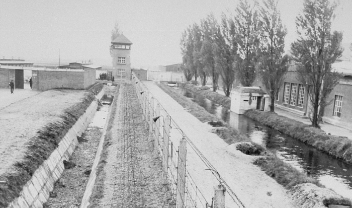 A guard tower is in the distance, with the insurmountable installation in front of it. To the right of the strip of grass adjoining the camp grounds is the two-meter deep ditch; on its other side is the barbed-wire obstacle. The barbed-wire fence is the final element in the well-secured installation. On the other side of the fence is a path that runs parallel to a small river, the Würm; on its opposite bank are buildings belonging to the SS grounds.