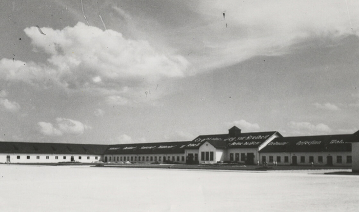 """The black-and-white photograph shows the maintenance building. In 1939 a quote from Heinrich Himmler was painted in large white letters on the side of the maintenance building roof facing the roll call area and the barracks: """"There is one path to freedom. Its milestones are: obedience, honesty, cleanliness, sobriety, diligence, order, self-sacrifice, truthfulness, love of the fatherland."""""""