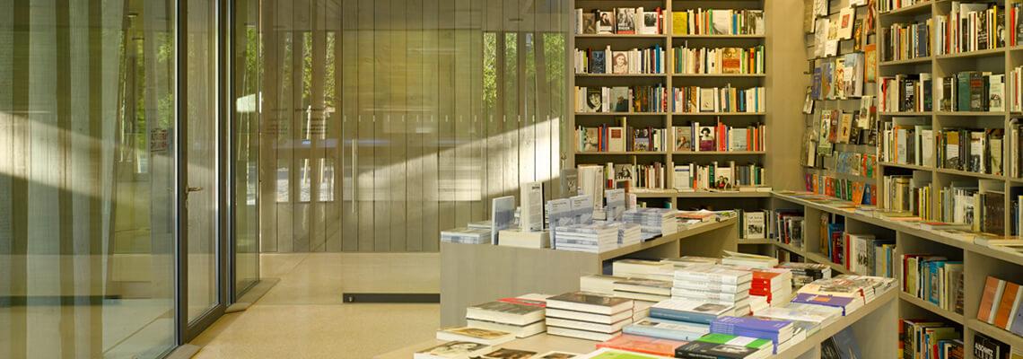 """Foto della libreria """"Literaturhandlung"""" in cui si vedono libri esposti sui tavoli e negli scaffali; la libreria si trova all'interno del centro visitatori del memoriale del campo di concentramento di Dachau"""